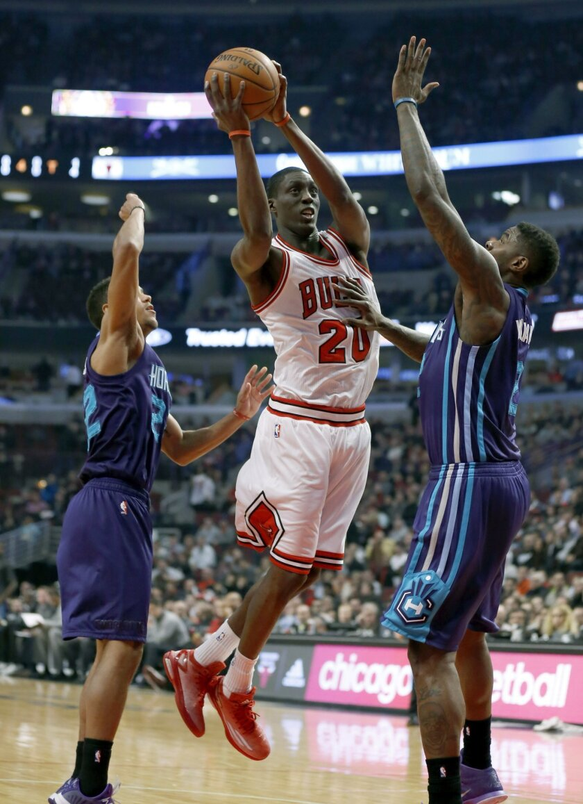 Chicago Bulls forward Tony Snell (20) drives between Charlotte Hornets guard Brian Roberts (22) and Marvin Williams during the first half of an NBA basketball game Wednesday, Feb. 25, 2015, in Chicago. (AP Photo/Charles Rex Arbogast)