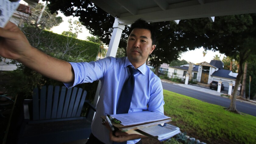 Los Angeles City Council candidate David Ryu leaves a campaign flier at a house in December.
