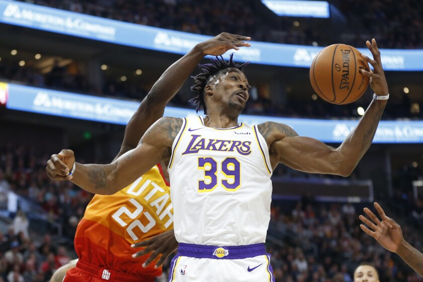 Lakers center Dwight Howard pulls down a rebound in front of Jazz forward Jeff Green (22) during the first half of a game Dec. 4 at Vivint Smart Home Arena.