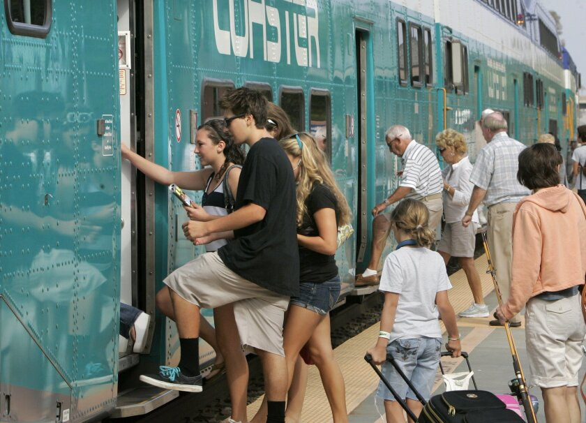 Coaster passengers can now buy train tickets on their Android smartphones. In this U-T San Diego file photo, riders board a southbound Coaster train at the Carlsbad Village Station. Photo by Charlie Neuman.