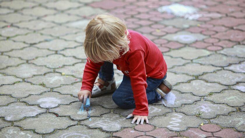 Preschooler child drawing with chalk on sidewalk daycare nursery generic web stock