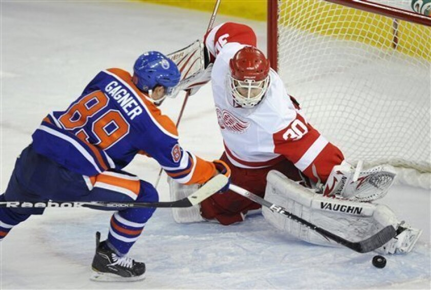 Detroit Red Wings goalie Chris Osgood, right, deflects a shot from Edmonton Oilers' Sam Gagner during the second period of an NHL hockey game in Edmonton, Alberta, on Tuesday, Jan. 4, 2011. (AP Photo/The Canadian Press, John Ulan)