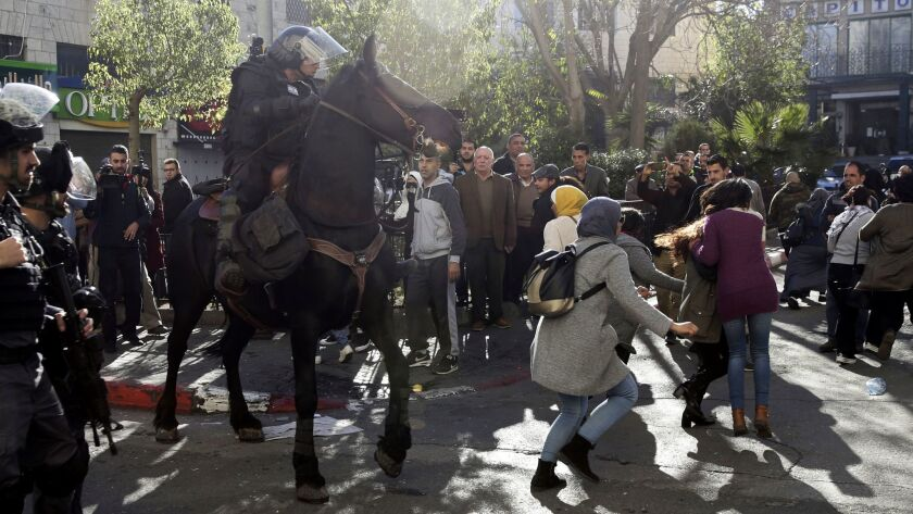 An Israeli mounted police officer charges Palestinians in Jerusalem on Saturday during a protest against President Trump's decision to recognize the city as the capital of Israel.