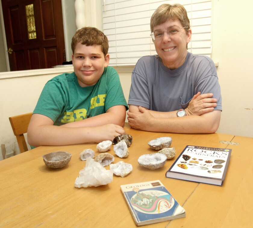 Kelly Duenckel and her son Robert Duenckel at home with some of the geodes and geology books in his collection.