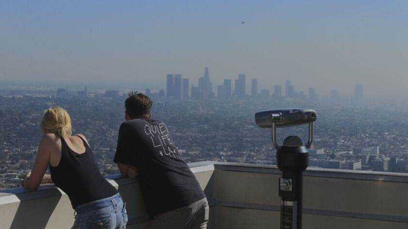 In this 2014 photo, visitors to Griffith Park north of Dodgers Stadium take in a smoggy Los Angeles Basin.