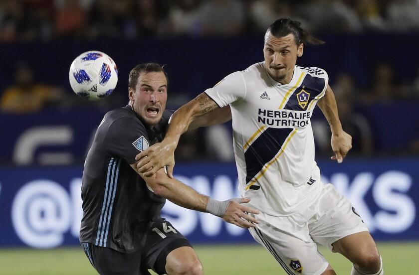 En esta foto de archivo del 11 de agosto de 2018, Zlatan Ibrahimovic (derecha), del Galaxy de Los Ángeles, persigue un balón, junto a Brent Kallman, del Minnesota United, en un partido de la MLS.
