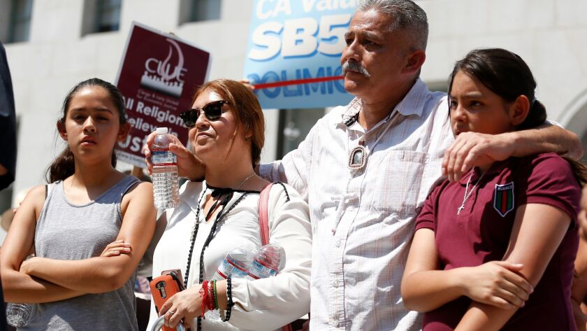 Romulo Avelica Gonzalez, an immigrant in the country illegally, and his family held a news conference in downtown Los Angeles on Thursday. Six months ago, he was arrested while taking his daughters to school in Lincoln Heights.