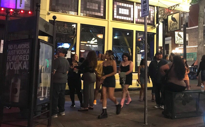 In this file photo from last weekend, Gaslamp Quarter visitors ignored social-distancing orders and didn't wear masks.