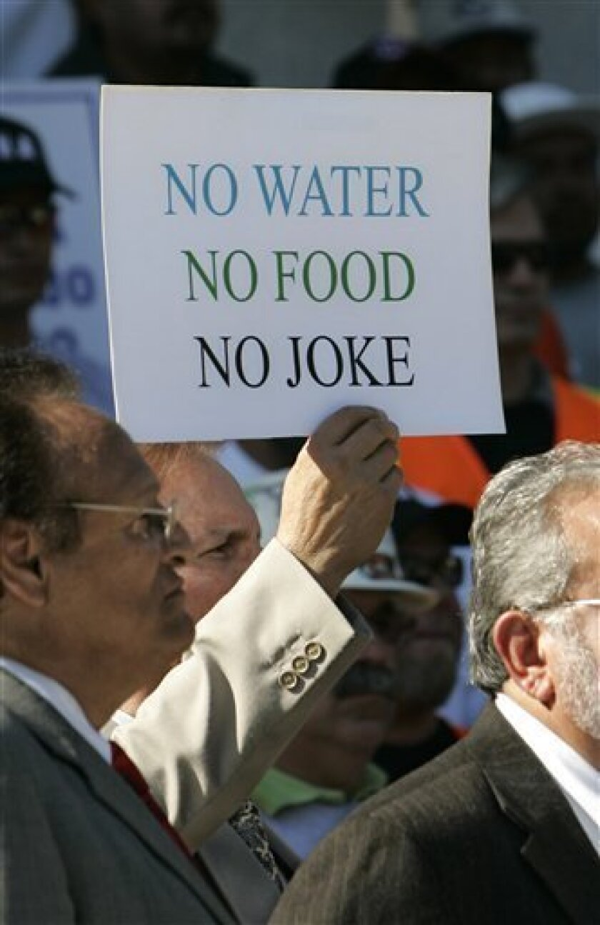 FILE - In this Friday, Oct. 9, 2009 file photo, a protest sign is seen at a rally attended by an estimated 200 farm workers and members of a Hispanic water coalition calling on Gov. Arnold Schwarzenegger and state lawmakers to reach a solution to the state's water problem at the Capitol in Sacramento., Calif., (AP Photo/Rich Pedroncelli, file)