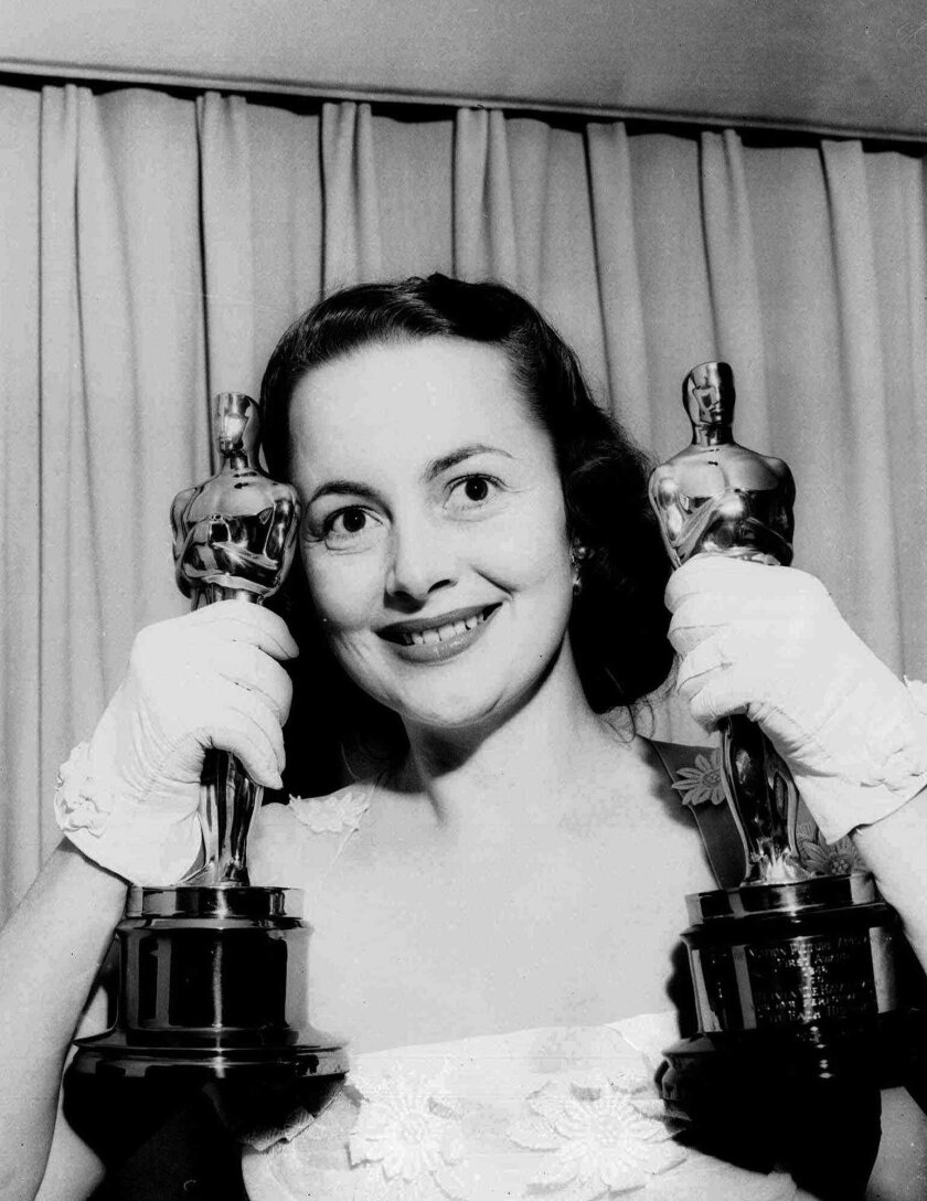 Olivia de Havilland holds her two Academy Award statuettes at her home after the Academy Awards ceremony in March 1950.