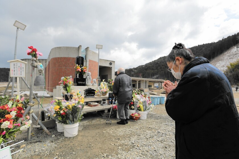 A woman offers prayers at Okawa Elementary School in Japan on the third anniversary of the March 11, 2011, earthquake and tsunami. Seventy-four of the school's 108 students died in the disaster.