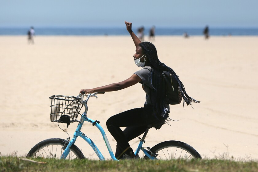 A woman bikes along the Venice Beach Boardwalk on a hot day this summer.