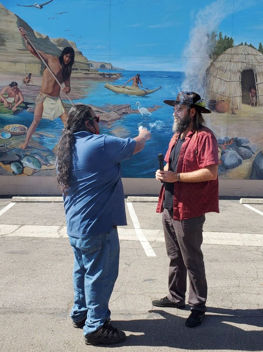 Mesa Grande Tribal Chairman Jesse Morales, left, offers a sage blessing to artist Simon Melnyk at Kumeyaay mural dedication.