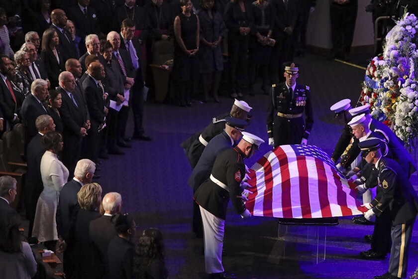 A military honor guard drapes a U.S. flag on the casket of Rep. Elijah Cummings.