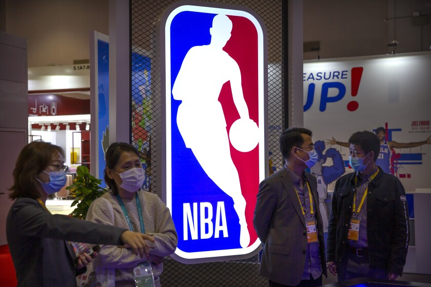 Visitors wearing face masks to protect against the coronavirus look at a display from the National Basketball Association (NBA) at the China International Import Expo in Shanghai, Thursday, Nov. 5, 2020. The expo, one of China's largest annual trade fairs, kicked off on Thursday as the ongoing COVID-19 pandemic has largely been controlled within China. (AP Photo/Mark Schiefelbein)