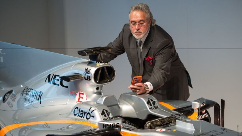 Businessman Vijay Mallya takes a picture of the Sahara Force India Formula One car for the 2017 season at a launch event at the Silverstone motor racing circuit near Towcester, central England, on Feb. 22, 2017.