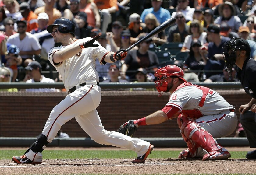 San Francisco Giants' Andrew Susac, left, hits a three-run home run in front of Philadelphia Phillies catcher Cameron Rupp during the fourth inning of a baseball game in San Francisco, Sunday, July 12, 2015. (AP Photo/Jeff Chiu)