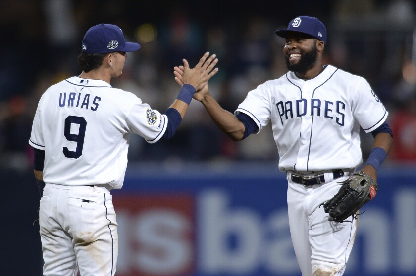 Luis Urias and Manuel Margot celebrate after the Padres defeated the Colorado Rockies 9-3 Thursday at Petco Park.