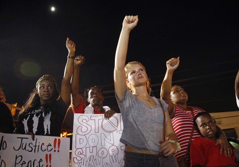 Ella Carr, al centro, de Austin, Texas, levanta un puño durante un mítin nocturno en honor de Alton Sterling, afuera del minisúper Triple S Food en Baton Rouge, Louisiana, (AP Foto/Gerald Herbert)
