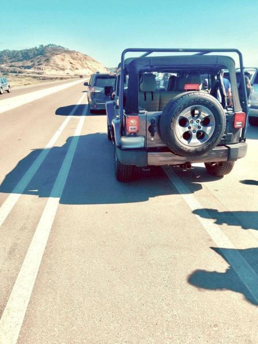 Several vehicles are seen parked over the bike lane in the Torrey Pines State Beach area.