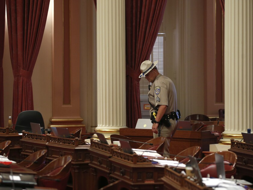 A CHP officer inspects desks in the California Senate chamber