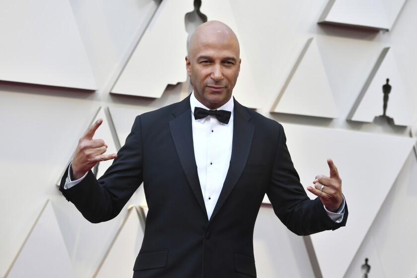 A bald man in a black tuxedo and bow tie makes rock-on symbols with his hands