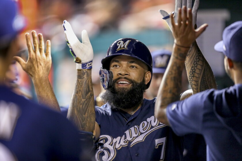 FILE - In this Oct. 1, 2019, file photo, Milwaukee Brewers' Eric Thames high fives teammates after hitting a solo home run during the second inning of a National League wild card baseball game against the Washington Nationals at Nationals Park in Washington. (AP Photo/Andrew Harnik, File)