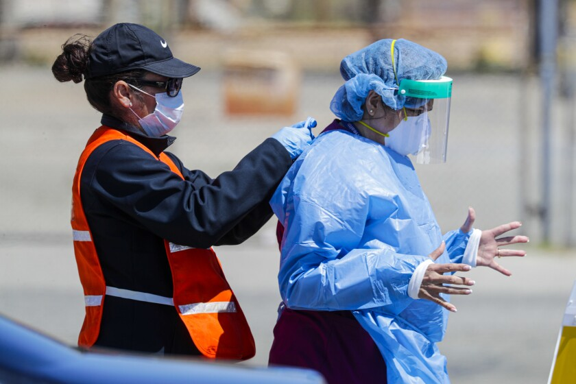 A drive-through coronavirus sample collection takes place at the Riverside County Fairgrounds in Victorville this month.