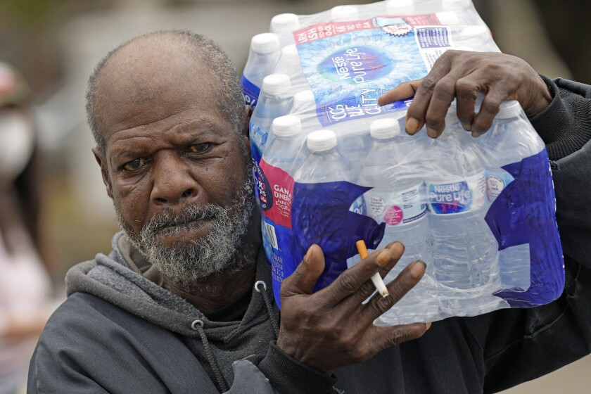 Kenneth Henderson carries a case of donated water back to his home, which was without running water after the recent winter storm, Friday, Feb. 26, 2021, in Houston. Local officials, including Houston Mayor Sylvester Turner, say they have focused their efforts during the different disasters on helping the underserved and under-resourced but that their work is far from complete. (AP Photo/David J. Phillip)