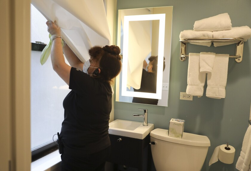 Maria Medina cleans a guest bathroom at Chicago's St. Clair Hotel, which recently improved its hygiene protocols as a result of the coronavirus crisis.