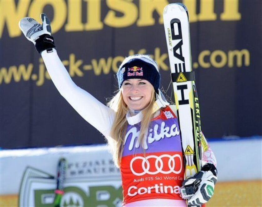 FILE - In this Saturday, Jan. 19, 2013 file photo, Lindsey Vonn, of the United States, celebrates at the finish area after winning an Alpine Ski World Cup women's downhill, in Cortina D'Ampezzo, Italy. Lindsey Vonn has won her sixth straight World Cup downhill title after thick fog forced the scheduled final race to be cancelled on Wednesday March 13, 2013. Five weeks after her season was ended by a serious knee injury, Vonn has retained her title by a single point from Tina Maze of Slovenia. (A