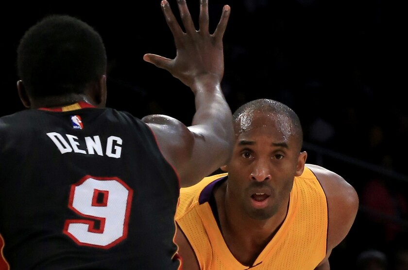 Kobe Bryant looks past the outstretched hand of Heat forward Luol Deng during the first quarter of a game Tuesday against Miami at Staples Center.