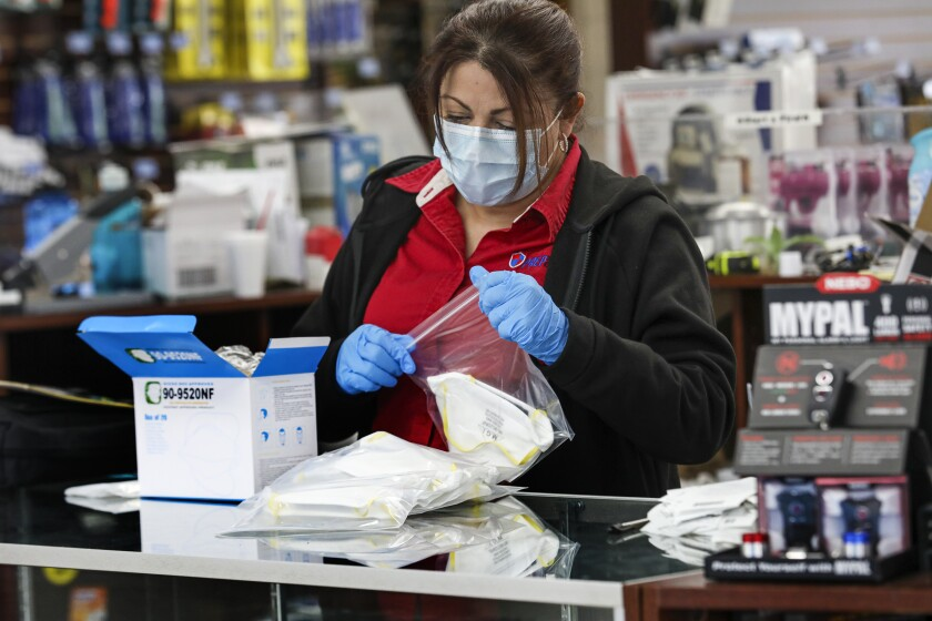 Teresa Olivas prepares single face mask bags at Prep & Save store in Upland.
