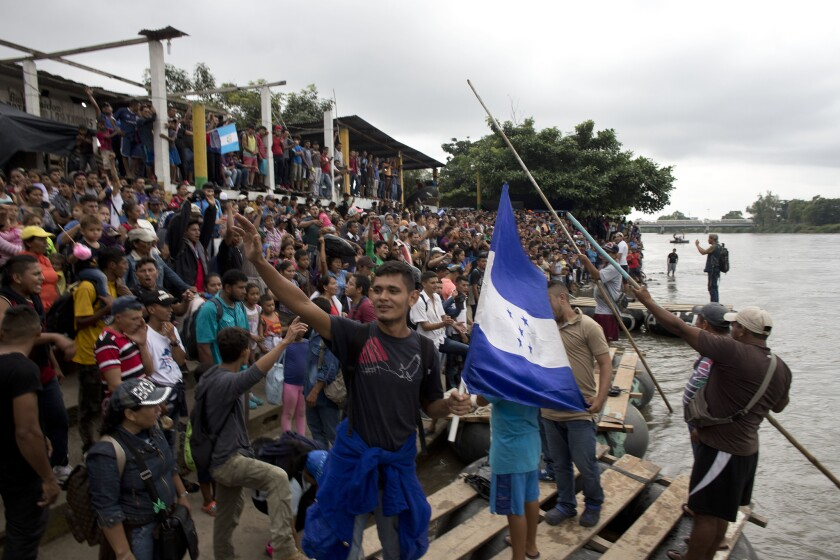 Hundreds of Honduran migrants stand at the shore of the Suchiate river on the border between Guatemala and Mexico.