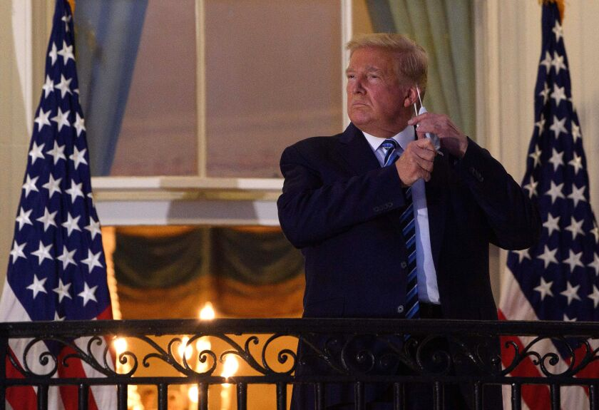 President Trump, stricken with COVID-19, removes his mask after arriving at the White House