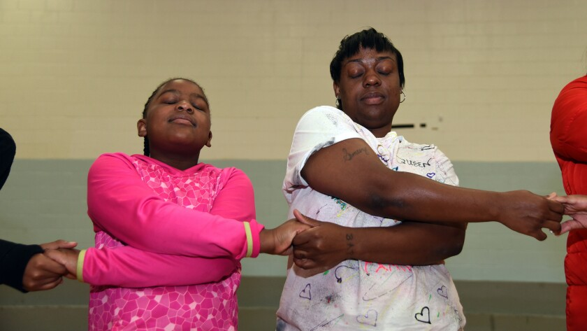 Kuhmaria VanBuren, 9, and her mom, Sapphire VanBuren, stand with others in a circle and make wishes at the Maryland Correctional Institution for Women.