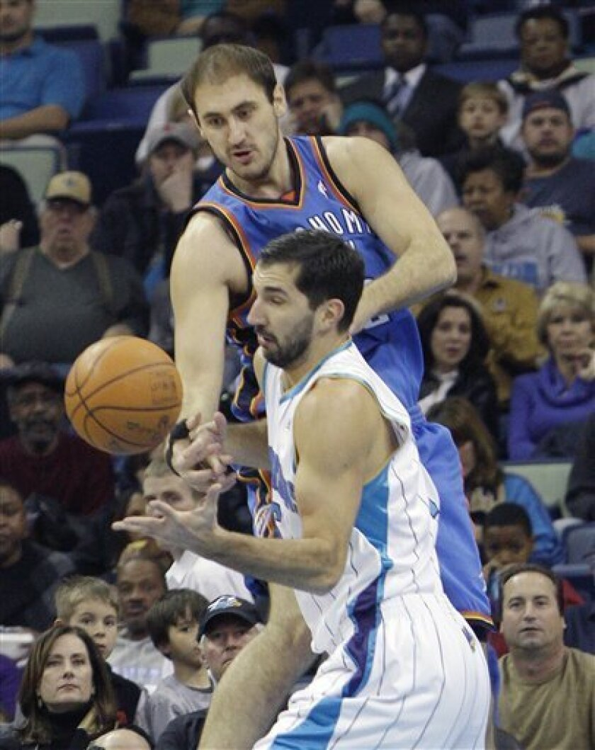 Oklahoma City Thunder center Nenad Krstic, rear, battles New Orleans Hornets forward Peja Stojakovic (16) for a loose ball in the first half of an NBA basketball game in New Orleans, Wednesday, Feb. 3, 2010. (AP Photo/Bill Haber)
