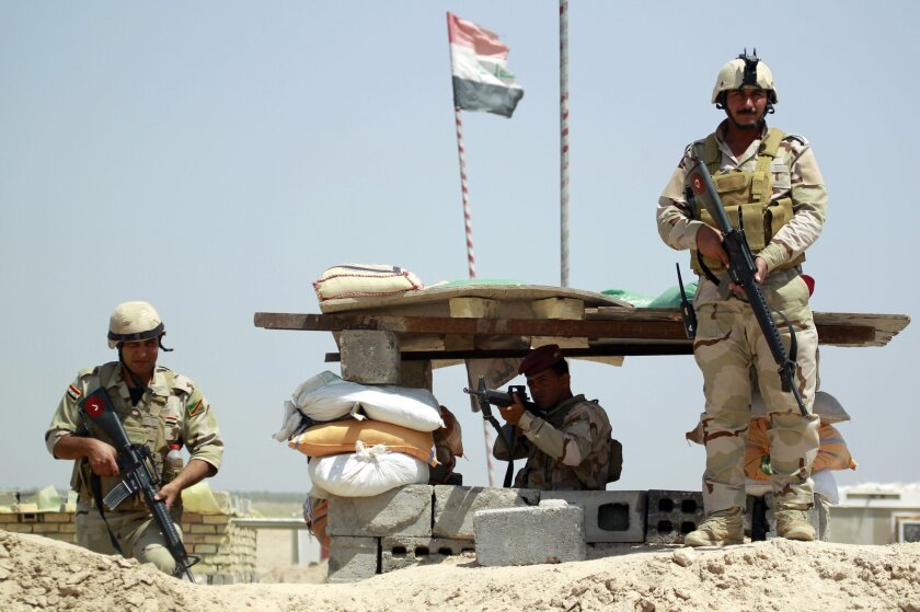 Iraqi government forces pose for a picture at a checkpoint in the Jurf al-Sakher area about 30 miles south of Baghdad.