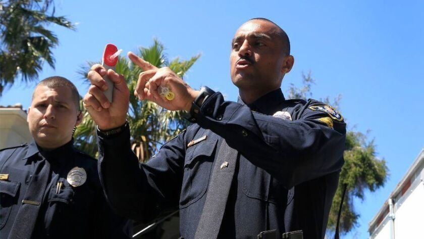 San Diego Police Officer and Drug Recognition Expert, Emilio Rodriguez demonstrates how a swab is placed into the Drager 5000, a portable drug analyzer. The portable analyzer detects the presence o