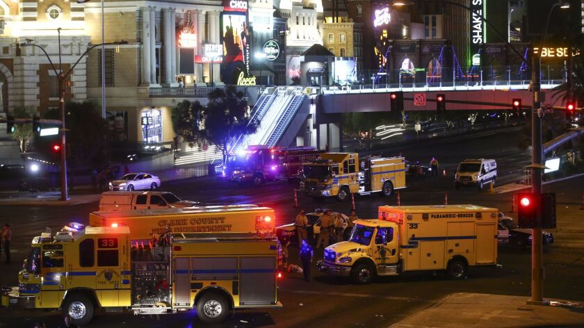 Emergency vehicles sit at the scene early Monday after a deadly shooting at a music festival on the Las Vegas Strip.