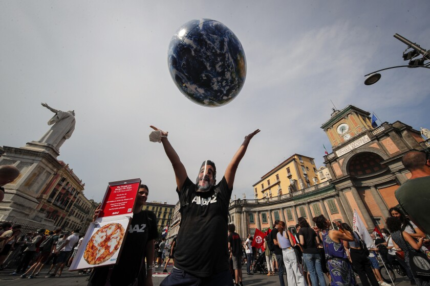 FILE - In this Thursday, July 22, 2021 file photo, people demonstrate on the sidelines of a G20 environment meeting, in Naples, Italy. A coalition of environmental groups called Tuesday, Sept. 7, 2021 for this year's climate summit to be postponed, arguing that too little has been done to ensure the safety of participants amid the continuing threat from COVID-19. The Climate Action Network, which includes more than 1,500 organizations in 130 countries, said there is a risk that many government delegates, civil society campaigners and journalists from developing countries may be unable to attend because of travel restrictions. The UN climate conference, known as COP26, is scheduled for early November in Scotland. (AP Photo/Salvatore Laporta, File)