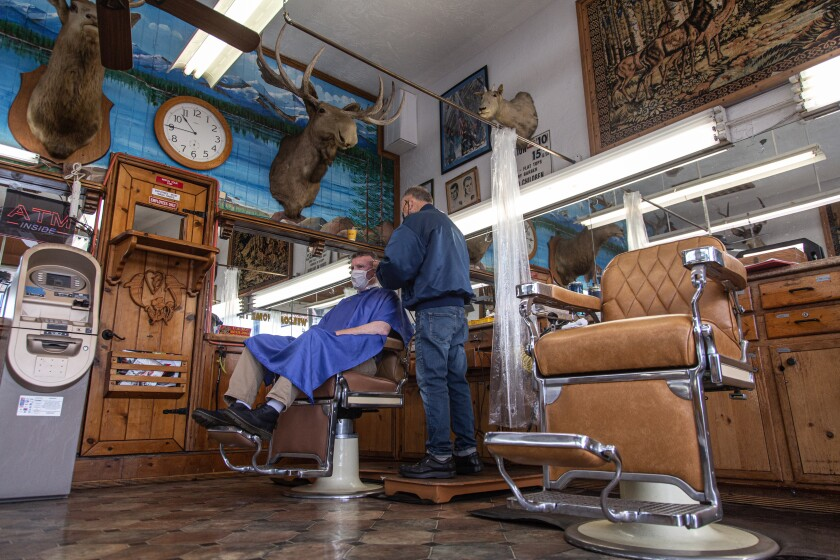 Adam Lyttle gets a haircut by Johnny Gomez, 83, at Esquire Barber Shop in Oceanside.