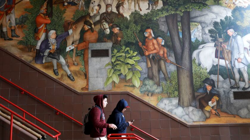 Students walk down stairs in front of a high school's mural of Native Americans and white settlers
