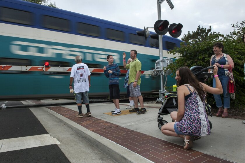 Pedestrians wait to cross the rail tracks on Carlsbad Village Drive in this undated photo.