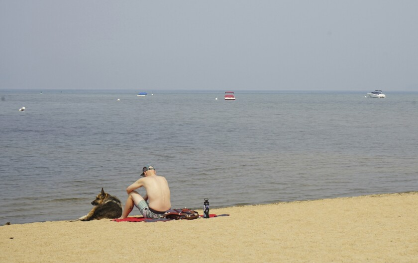 South Lake Tahoe resident Connor Jones sits with his dog on a smoke-cloaked empty beach in South Lake Tahoe, Calif., Monday Sept. 6, 2021. Residents who fled South Lake Tahoe under threat of a wildfire were allowed to return as crews stalled the flames from advancing. (AP Photo/Samuel Metz)
