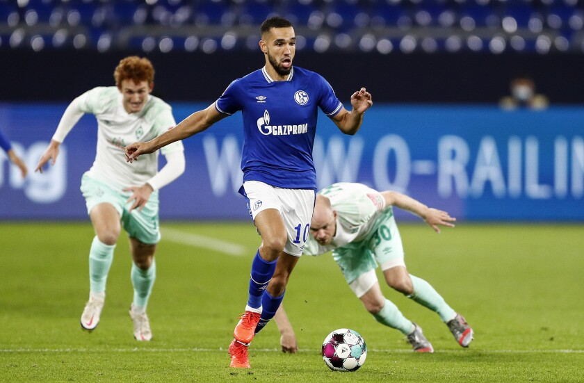 """FILE - In this Satuday, Sept. 26, 2020 file photo, Schalke's Nabil Bentaleb runs for the ball during the German Bundesliga soccer match between FC Schalke 04 and Werder Bremen in Gelsenkirchen, Germany. Bundesliga bottom side Schalke has plunged further into chaos with the departure of its technical director and suspension of three players. The club says one of the players, experienced striker Vedad Ibisevic, is to have his contract dissolved with effect from Dec. 31. Algeria midfielder Nabil Bentaleb is to leave at the end of the season """"at the latest."""" Moroccan midfielder Amine Harit was also suspended. He and Bentaleb are to train individually """"until further notice."""" (AP Photo/Martin Meissner, File)"""
