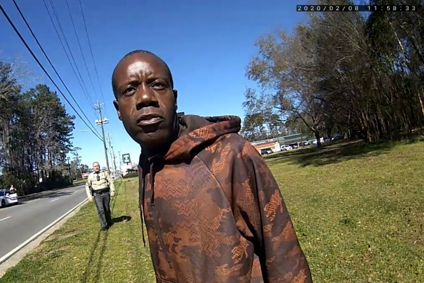 FILE - In this still image from a body camera video released by the Valdosta police, Antonio Arnelo Smith speaks to an officer as Sgt. Billy Wheeler approaches him from behind in Valdosta, Ga., on Feb. 8, 2020. The video shows Smith handing his driver's license to a police officer and answering questions cooperatively before Wheeler wraps him in a bear hug and slams him face-first to the ground. Smith is crying in pain when he's told there's a warrant for his arrest. Officers are then told the warrant was for someone else. Valdosta's City Council on Thursday, June 11, 2021, approved an offer of $350,000, to settle an excessive force lawsuit Smith filed last year against Valdosta police and other city officials. (Valdosta Police via AP, File)