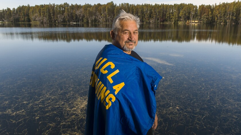 Zenon Andrusyshyn dons his UCLA football raincoat, at his home in Land O' Lakes, Fla. The son of Ukrainian parents, Andrusyshyn was born in a German refugee camp and migrated with his family to Canada when he was 3 years old.