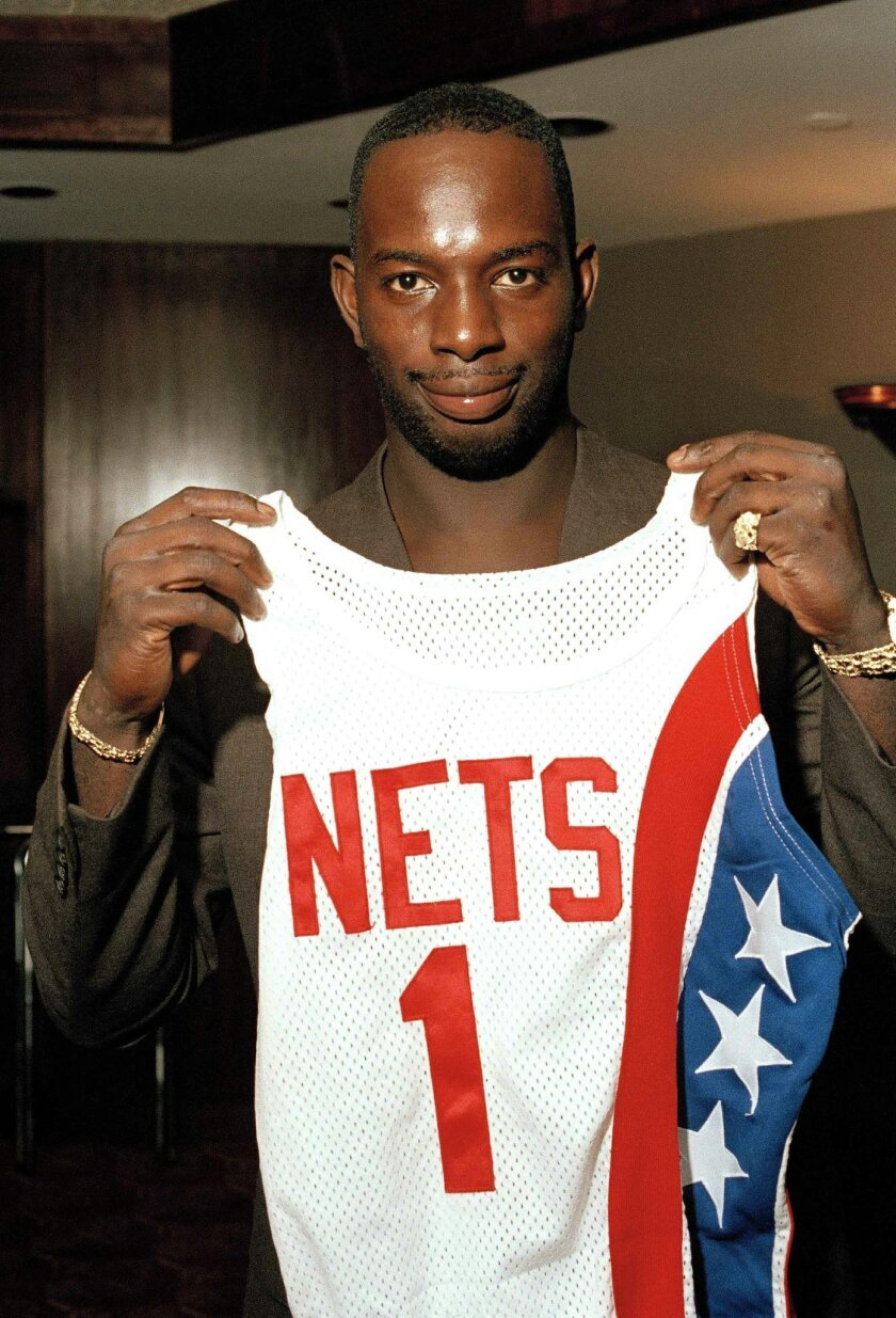 "FILE - In this Aug. 20, 1986 file photo, Dwayne ""Pearl"" Washington, the first draft pick by the New Jersey Nets, holds up his new uniform during a press luncheon at the Meadowlands Arena in East Rutherford, N.J.  Washington, who went from New York City playground wonder to Big East star for Jim Boe"