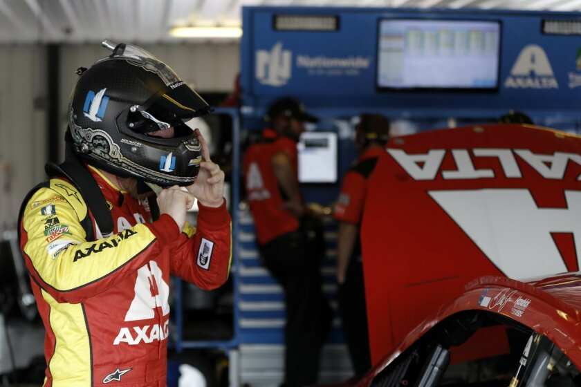 Dale Earnhardt Jr. removes his helmet after a practice session for Sunday's NASCAR auto race, Saturday, June 4, 2016, in Long Pond, Pa. (AP Photo/Matt Slocum)